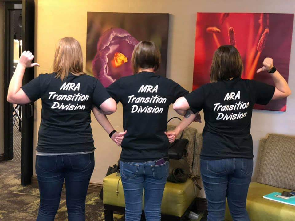 """Three women with their backs facing the camera. Arms are interlinked and they are pointing to the back of black t-shirts, which says """"MRA Transition Division"""" in white."""